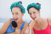 Friends in hair rollers singing into their hairbrushes — Stock Photo