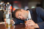 Unconscious businessman holding whiskey glass lying on a counter — Stock Photo