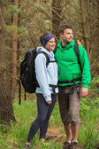 Smiling couple standing in a forest — Stok fotoğraf