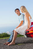 Smiling couple sitting on their cabriolet car hood — Stock Photo