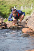 Hiker bending to take a drink from the stream — Stock Photo