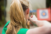 Rear view of blonde about to shoot arrow — Stock Photo