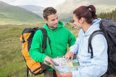 Happy couple resting after hiking uphill and consulting map — Стоковое фото
