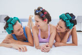 Laughing friends lying in bed — Stock Photo