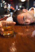 Unconscious businessman holding whiskey lying on a counter — Stock Photo