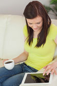 Smiling girl sitting on a sofa using a tablet pc and holding a cup of coffee — Stock Photo