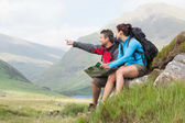 Couple taking a break after hiking uphill and holding map — Stok fotoğraf