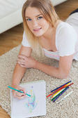 Smiling young woman lying on floor sketching on paper — Stock Photo