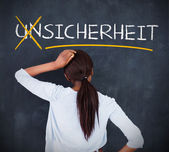 Woman looking at a chalkboard with sicherheit on it — Stock Photo