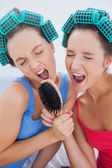 Friends in hair rollers holding hairbrush — Stok fotoğraf