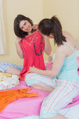 Happy girls looking at a dress at a sleepover — Stock Photo