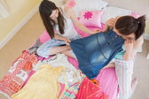 Cute girls looking at a denim dress at a sleepover — Stock Photo