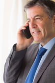 Serious man calling someone with his mobile phone — Stock Photo