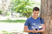 Smiling handsome student using his digital smartphone — Stock Photo