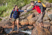 Man helping his smiling girlfriend to cross a river — Stock Photo