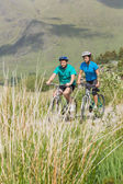 Athletic couple cycling together — Stock Photo