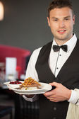 Handsome waiter serving appetizing duck dish — Stock Photo