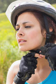Athletic woman adjusting her bike helmet — Stock Photo