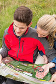 Cheerful couple taking a break on a hike to look at map and compass — Stock Photo