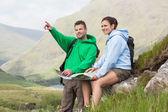 Coppia riposo dopo trekking in salita e consulenza mappa — Foto Stock