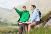 Couple de repos après une randonnée en montée et consulter la carte — Photo