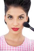 Gorgeous black hair model applying powder on her cheek — Stock Photo