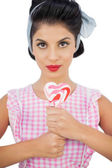 Charming black hair model holding a heart shaped lollipop — Stock Photo
