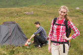 Cheerful woman carrying backpack while boyfriend is pitching tent — Stock Photo