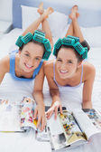 Happy friends in hair rollers lying in bed — Stock Photo