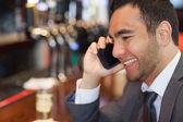 Veselá pohledný podnikatel na telefonu s drink — Stock fotografie