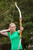 Concentrating blonde woman practicing archery — Stock Photo