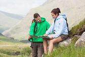 Coppia di riposo dopo trekking in salita e guardando la mappa — Foto Stock