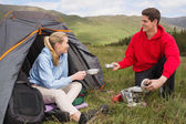 Happy couple cooking outdoors on camping trip — Stock Photo