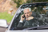 Content businessman on the phone driving expensive cabriolet — Stock Photo