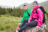 Paar zittend op een rots rusten tijdens wandeling — Stockfoto
