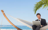 Businessman sitting in hammock using laptop looking at camera — Stock Photo