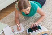 Blonde woman lying on floor using tablet to do her assignment — Stock Photo