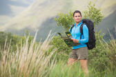 Attractive female hiker with backpack holding a map — Stock Photo