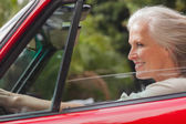 Smiling mature woman driving red convertible — Stock Photo
