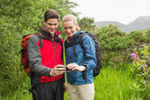 Happy couple on a hike looking at photo on smartphone — Stock Photo