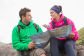 Couple using map and compass sitting on a rock — Stock Photo