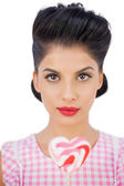 Unsmiling black hair model holding a heart shaped lollipop — Stock Photo