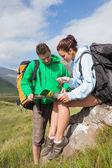 Atractiva pareja descansando después de caminar cuesta arriba y consultoría mapa — Foto de Stock