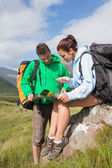 Attractive couple resting after hiking uphill and consulting map — Стоковое фото
