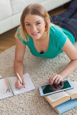 Cheerful young woman lying on floor using tablet to do her assignment — Stock Photo