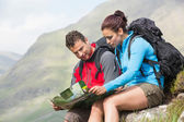 Couple resting after hiking uphill and reading map — ストック写真