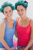 Girls in hair rollers sitting in bed and smiling — Stock Photo