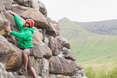 Focused man scaling a large rock face — Stock Photo