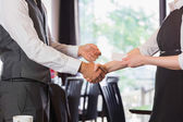 Business team shaking hands and swapping card — Stock Photo