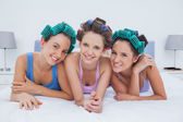 Girls in hair rollers lying in bed — Stock Photo
